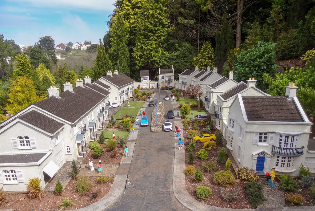model of cul de sac full of two-story homes and children playing on the sidewalks