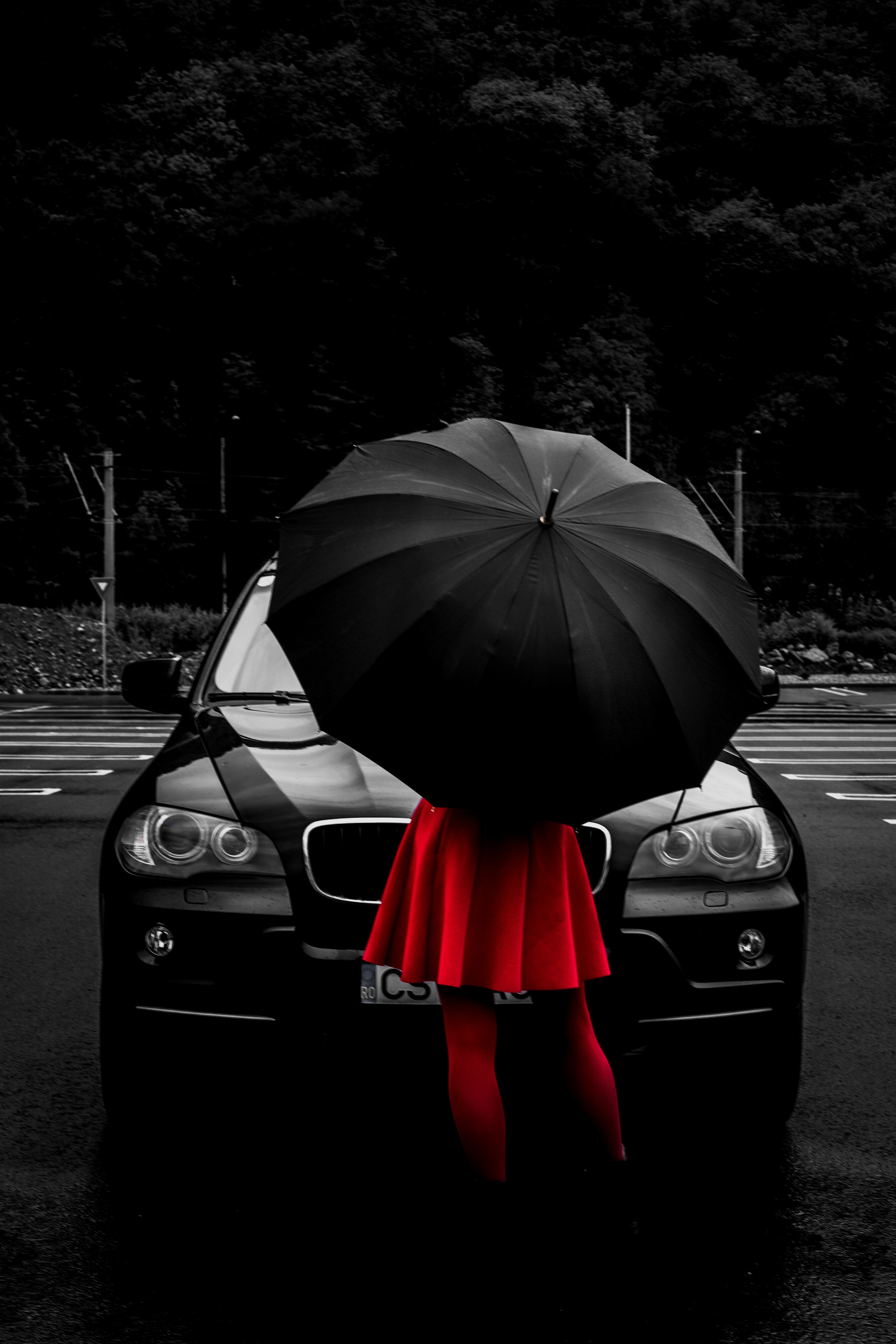 black car facing camera with female in red dress and red tights holding black umbrella standing facing car
