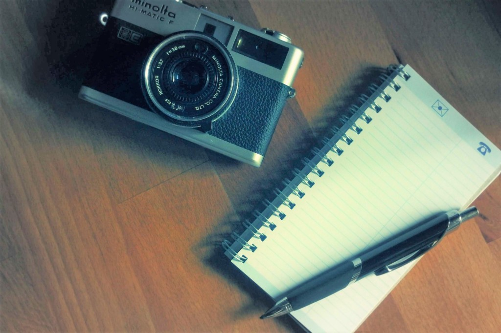 wooden surface with old-fashioned camera next to small notebook with ballpoint pen on top