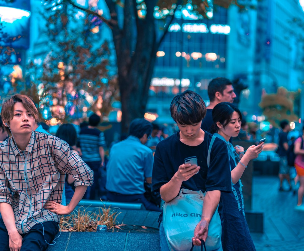 Asians in city setting looking at phone and wearing headphones.
