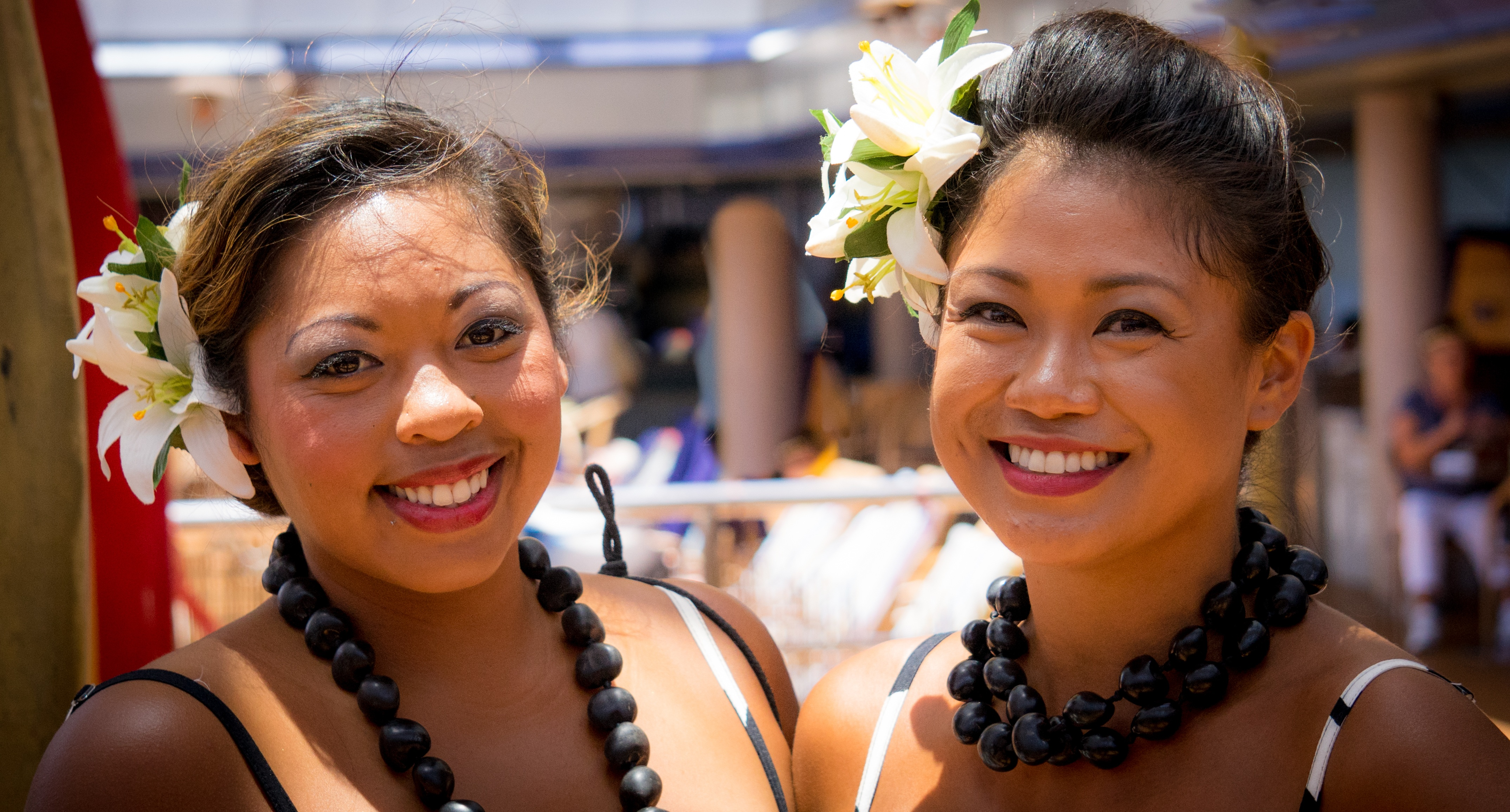 two smiling dark-haired ladies wearing white flowers in their up-swept hair, strappy tops, and kukui nut leis