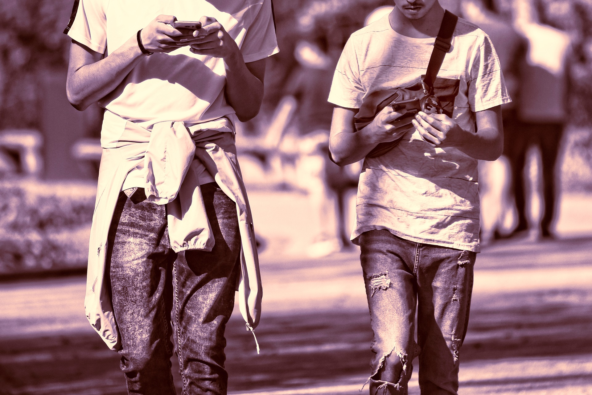 sepia photo of two guys in t-shirt and jeans walking while using phones
