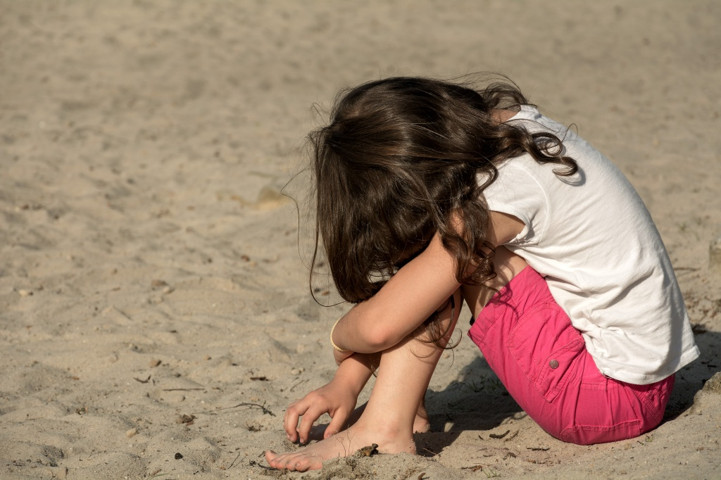 brown-haried girl in white t-shirt and dark pink shorts sitting on beach with head on knees