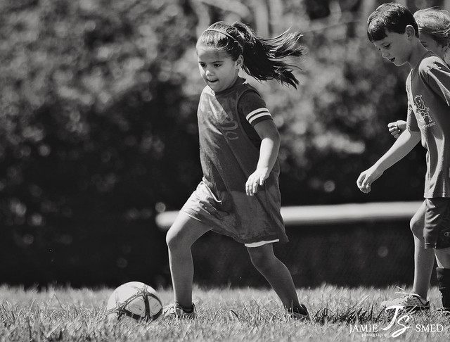 black and white photo of kids playing soccer in park