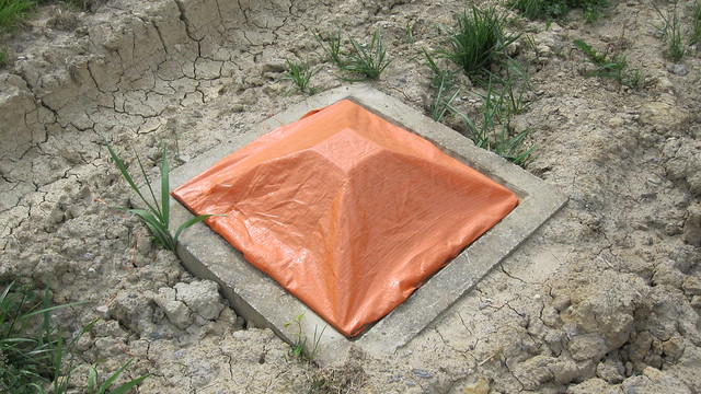 tarp covering a large ground drain