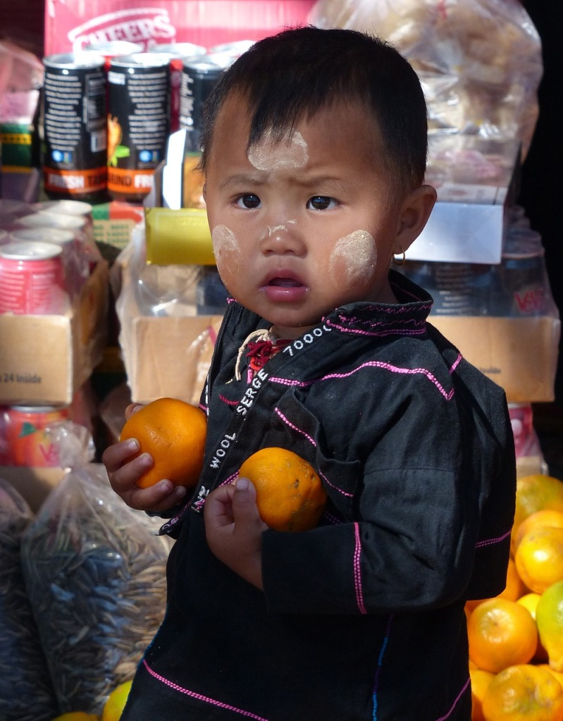 Asian child holding two tangerines, with flour-like smudges on his face