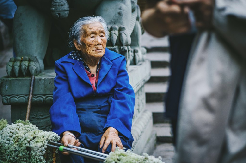 old Asian woman in blue coat sitting in front of stone statue