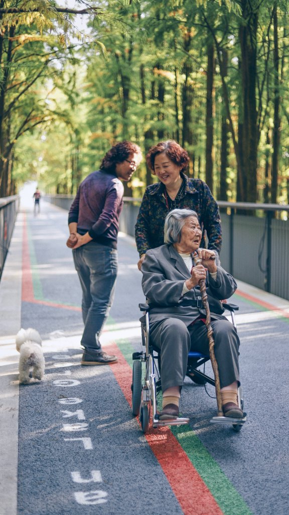three Asian women and a small dog on a pedestiran path, one is pushing an elderly woman in a wheelchair